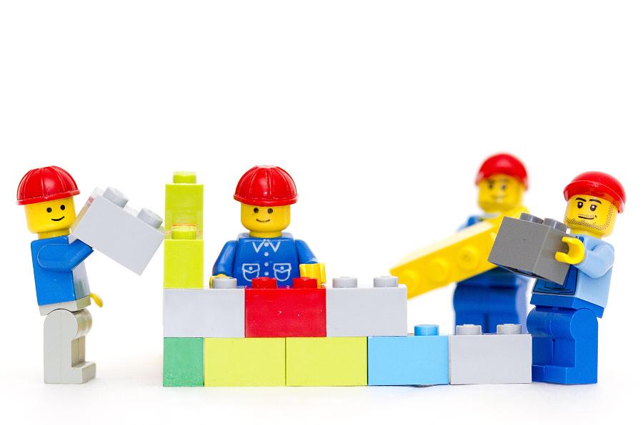 LEGO men building a wall.