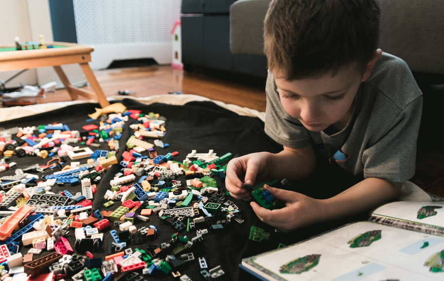 A young boy following reading the instructions booklet of a lego set